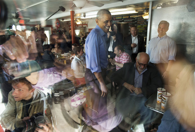President Barack Obama, center, and Austin, Texas Mayor Steve Adler, right, greet patrons during an unannounced stop at Torchy's Tacos, Friday, March 11, 2016, in Austin, Texas. Obama traveled to Austin, to speak at South by Southwest Festival (SXSW) and attend two Democratic National Committee fundraisers. (Photo by Pablo Martinez Monsivais/AP Photo)