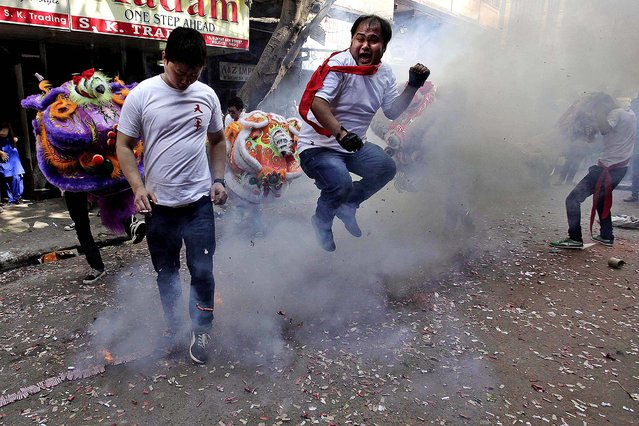 A Chinese youth of Indian origin jumps over exploding firecrackers during Chinese New Year celebrations in Kolkata, India. (Photo by Bikas Das/Associated Press)