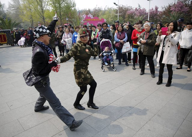 Seventy-nine-year-old Wang Baorong, dressed in military style clothes, dances with a man as she performs square dancing at a park square in Beijing, China, April 9,  2015.  Chinese-style square dancing is running circles around other hobbies for the elderly, with millions taking to parks and plazas across China, swivelling their hips and rolling their arms – but it's not to everyone's liking. (Photo by Kim Kyung-Hoon/Reuters)