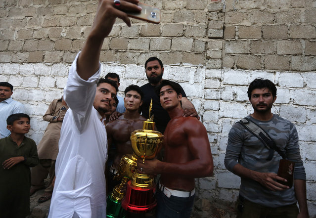 Locals pose for a selfie with the winner at a local bodybuilding and fitness championship in Karachi, Pakistan March 13, 2016. (Photo by Akhtar Soomro/Reuters)