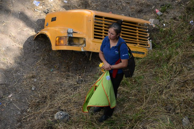 A woman watches rescue operations after a bus and a truck crashed on the road that links the Honduran capital with the south of the country, near Germania, 11 km south of Tegucigalpa on February 5, 2017. At least 12 people were killed and 35 injured of some 70 who were on board the bus. (Photo by Orlando Sierra/AFP Photo)