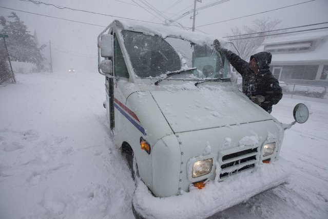 US postal worker Daniel DeCusace tries to clear the snow from his truck in Warwick, Rhode Island, USA, 09 February 2017 as a major snowstorm hits the region. (Photo by Lisa Hornak/EPA)