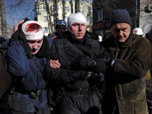 Two wounded policemen are guided to the ambulance cars during an anti-government protest in downtown Kiev. (Photo by Alexey Furman/EPA)