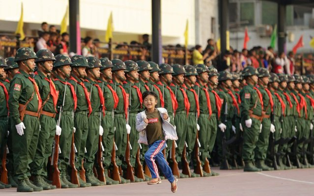 A young girl runs past UWSA military contingents before a parade held to mark the 30th anniversary of Wa State in Panghsang, also called Pang Kham of autonomous Wa region, north-eastern Myanmar, 17 April 2019. United Wa State Army (UWSA) celebrated the 30th anniversary of Wa State founding in Panghsang, the administrative capital of the Wa independent region. Wa declared itself as an independent State on 17 April 1989. Although the government of Myanmar does not recognize the sovereignty of Wa State, Myanmar military has adopted a ceasefire with the state since 09 May 1989. Wa State has been notorious for drug smuggling in the Golden Triangle of the last 30 years, although it declared its region a drug-free zone in 2005. (Photo by Lynn Bo Bo/EPA/EFE/Rex Features/Shutterstock)