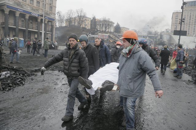 Activists carry a dead protester during clashes with police in Kiev's Independence Square, the epicenter of the country's current unrest, Kiev, Ukraine, Thursday, February 20, 2014. (Photo by Efrem Lukatsky/AP Photo)