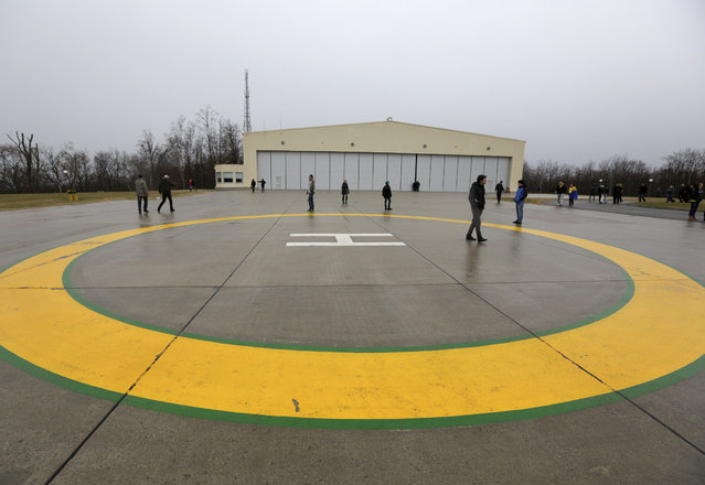 Anti-government protesters and journalists walk on a helipad at the Mezhyhirya residence of Ukraine's President Viktor Yanukovich in the village Novi Petrivtsi, outside Kiev February 22, 2014. (Photo by Konstantin Chernichkin/Reuters)