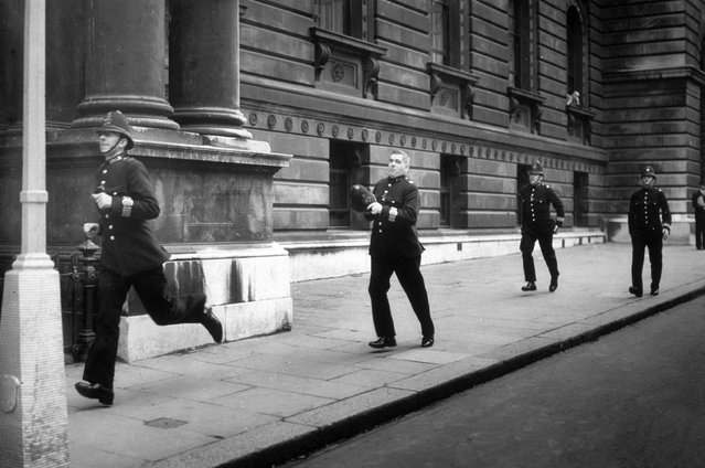 Police officers running along Downing Street, London, circa 1938. (Photo by Topical Press Agency/Getty Images)
