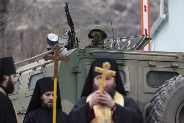 Orthodox monks pray near an armed serviceman in a Russian army vehicle outside a Ukrainian border guard post in the Crimean town of Balaclava March 1, 2014. (Photo by Baz Ratner/Reuters)