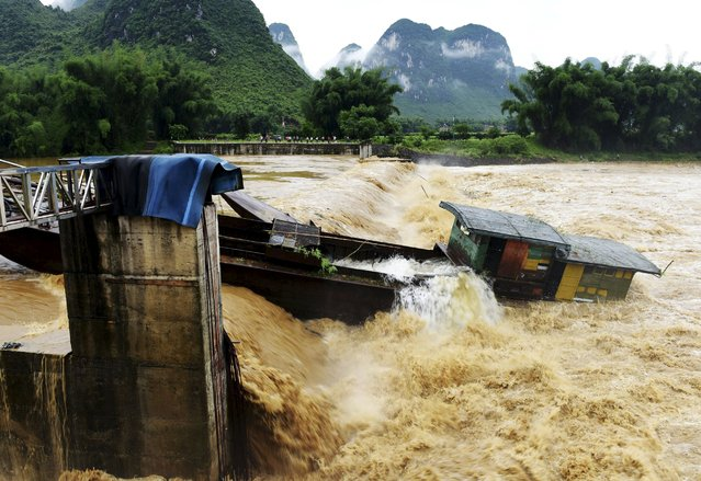 A boat is pushed down a dam by floodwater after heavy rainfall hit Luocheng Mulao Autonomous County, Guangxi Zhuang Autonomous Region, China, May 15, 2015. (Photo by Reuters/Stringer)