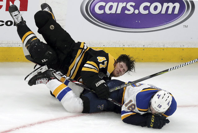 Boston Bruins' Torey Krug (47) and St. Louis Blues' Robert Thomas (18) crash to the ice during the third period in Game 1 of the NHL hockey Stanley Cup Final, Monday, May 27, 2019, in Boston. (Photo by Charles Krupa/AP Photo)
