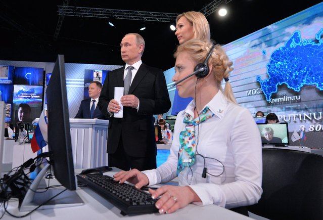 Russian President Vladimir Putin, center left, stands next to TV presenter Valeria Korablyova, during his marathon call-in TV show in Moscow, Russia on Thursday, April 14, 2016. The Russian leader uses the annual event to burnish his image as a strong leader who protects Russia from foreign threats and cares about people's needs. An unidentified phone operator sits at front. (Photo by Mikhail Klimentyev/Sputnik, Kremlin Pool Photo via AP Photo)