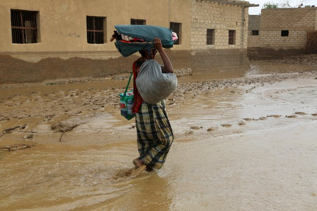 A man carries his belongings as he wades through a flooded street following heavy rain in a village in Yemen's Red Sea province of Houdieda April 15, 2016. (Photo by Abduljabbar Zeyad/Reuters)