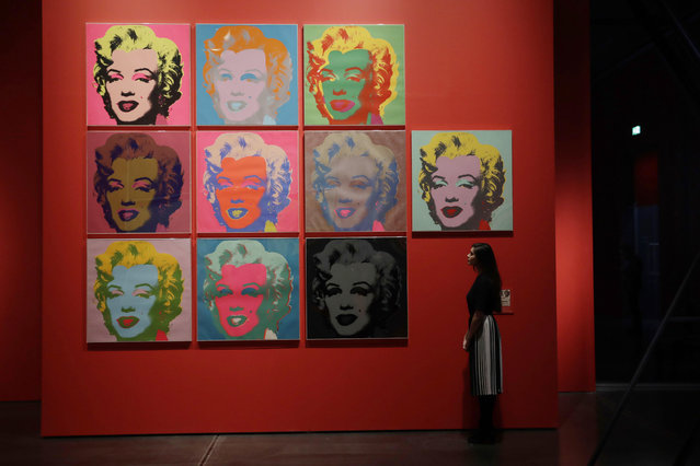 "A British Museum representative poses for photographs next to Andy Warhol's ""Marilyn 1967, 10 Color Screenprints"" which feature in ""The American Dream: pop to the present"" exhibition during a media photocall at the British Museum in London, Monday, March 6, 2017. (Photo by Matt Dunham/AP Photo)"
