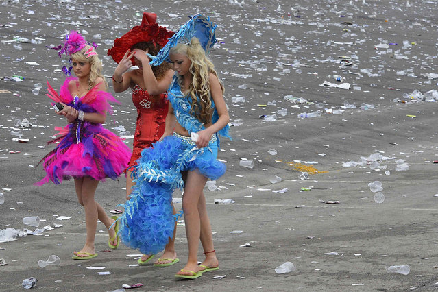 Racegoers walk through litter as they leave on Ladies' Day, the second day of the Grand National horse racing meeting at Aintree, northern England April 4, 2014. (Photo by Toby Melville/Reuters)