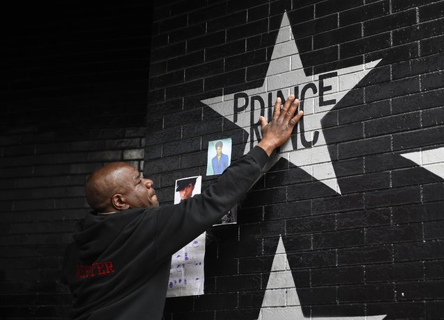 Donnie Straub of Minneapolis touches a star bearing U.S. music superstar Prince's name on an exterior wall of First Avenue, the nightclub where Prince got his start in Minneapolis, Minnesota, April 21, 2016. (Photo by Craig Lassig/Reuters)