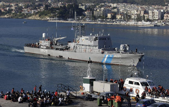 Greek coast guard vessels arrive with migrants after an operation as other migrants who arrived earlier wait to be counted by Greek authorities at the port of Mitylene on the northeast Greek island of Lesvos Wednesday, June 17, 2015. Around 100,000 migrants have entered Europe so far this year as Italy and Greece have borne the brunt of the surge with many more migrants expected to arrive from June through to September. (AP Photo/Thanassis Stavrakis)