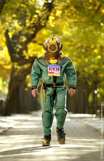Lloyd Scott wears a 140-pound antique diving suit while walking on Fifth Avenue as he attempts to finish the New York Marathon
