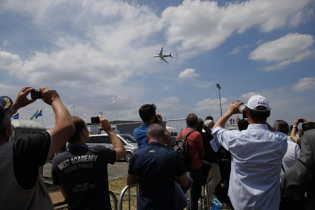 Onlookers take photos of the Airbus A 350 during its demonstration flight of the Paris Air Show, in Le Bourget airport, north of Paris, Tuesday, June 16, 2015. Some 300,000 aviation professionals and spectators are expected at this week's Paris Air Show, coming from around the world to make business deals and see dramatic displays of aeronautic prowess and the latest air and space technology. (AP Photo/Francois Mori)