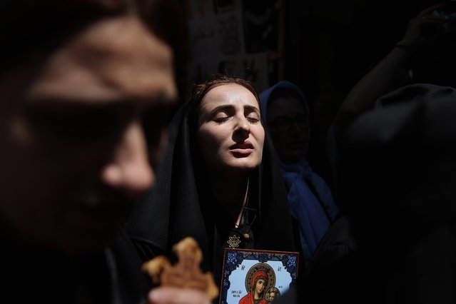 Orthodox Christian pilgrims from Abkhazia walk along the Via Dolorosa (Way of Suffering), during the Good Friday procession in Jerusalem's old city on April 29, 2016. Thousands of pilgrims took part in processions along the route where, according to tradition, Jesus carried the cross during his last days. (Photo by Gali Tibbon/AFP Photo)