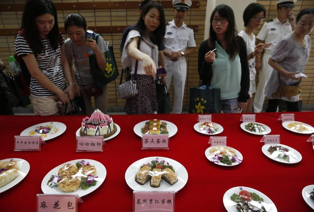 Visitors look at the Chinese banquet dishes at the open day of Stonecutter Island Navy Base of Chinese People's Liberation Army (PLA) in Hong Kong to mark the 18th anniversary of the Hong Kong handover to China in Hong Kong, Wednesday, July 1, 2015. (Photo by Kin Cheung/AP Photo)