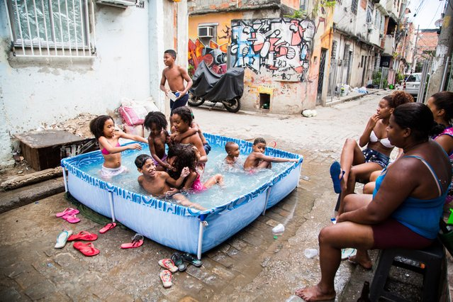 Bathing in a swimming pool on a summer's day in Nova Holanda, Maré. (Photo by Elisângela Leite/Horniman Museum)