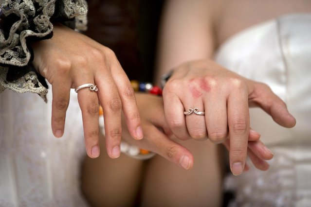Teresa Xu, left, and Li Tingting, right, show off their wedding rings before their wedding in Beijing, Thursday, July 2, 2015. (Photo by Mark Schiefelbein/AP Photo)