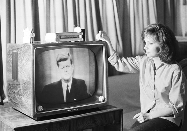 Gina Lollobrigida watchers President Kennedy on a television set in her Rome villa, July 23, 1962 during live telecast from the U.S. to Europe via the Telstar satellite. The Italian actress left the set of her present movie to watch the program which included a portion of the President's news conference, in Washington. (Photo by Jim Pringle/AP Photo)