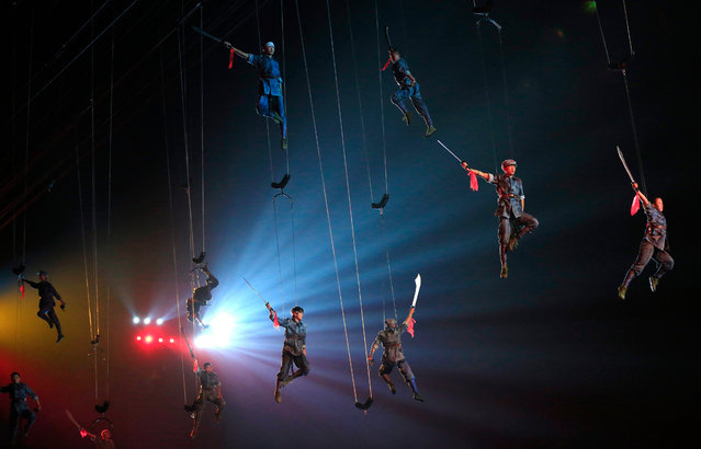 """Actors dressed as Communist Red Army soldiers perform hanging from wires during """"Mao Zedong Comes from China"""", a show based on the former Chinese Communist leader's life at an outdoor theater in Shaoshan, Hunan Province in central China, 27 April 2016. (Photo by How Hwee Young/EPA)"""
