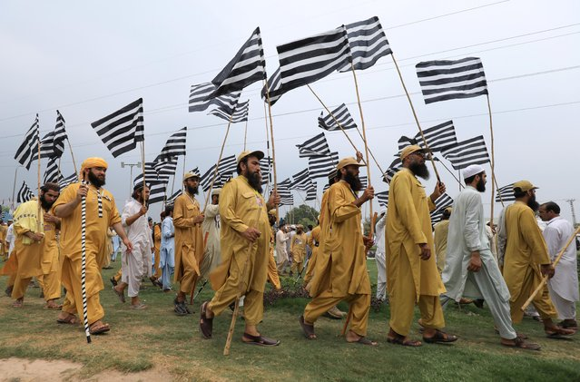 "Supporters of opposition political parties walk with flags during a countrywide protest called ""Black Day"" against the government of prime minister Imran Khan, in Peshawar, Pakistan on July 25, 2019. (Photo by Fayaz Aziz/Reuters)"