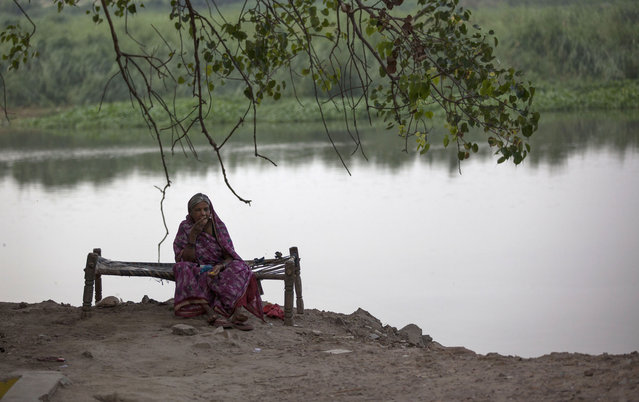 An elderly Indian woman sits by the River Yamuna in New Delhi, India, Tuesday, June 30, 2015. The Yamuna is one of the most polluted rivers in the world, especially around Delhi, due to rapid growth, urbanisation and waste dumping. (Photo by Tsering Topgyal/AP Photo)