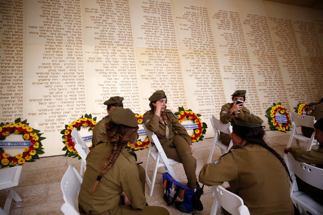 Israeli soldiers sit in front of a monument engraved with names of fallen Israeli soldiers, as they wait for the start of a ceremony marking Memorial Day in Jerusalem, May 10, 2016. Israel commemorates its fallen soldiers on Memorial Day, which begins Tuesday night. (Photo by Ronen Zvulun/Reuters)