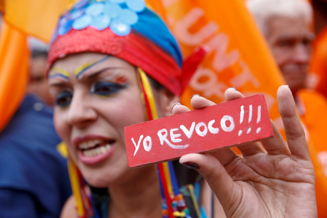 """An opposition supporters holding a sign that reads """"I recall"""" (in reference to the revocatory referendum) shouts during a rally to demand a referendum to remove President Nicolas Maduro in Caracas, Venezuela, May 11, 2016. (Photo by Carlos Garcia Rawlins/Reuters)"""