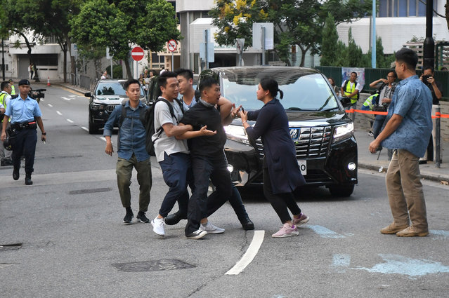 A protester (C) runs out in front of Hong Kong's Chief Executive Carrie Lam's motorcade outside Queen Elizabeth Stadium in the Wanchai district of Hong Kong on September 26, 2019, ahead of a planned town hall meeting between Lam and some 150 people picked via lottery after more than 20,000 people applied to attend the event. Hong Kong's embattled leader was to attend the two-hour meeting later in a bid to reach out to residents after more than three months of huge, sometimes violent pro-democracy protests. (Photo by Anthony Wallace/AFP Photo)