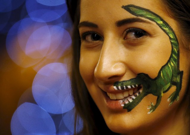 A girl is pictured with a dinosaur design painted on her face during a dinosaur-themed exhibition in Beirut, Lebanon, July 11, 2015. (Photo by Jamal Saidi/Reuters)