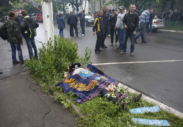 The body of a Ukrainian policeman is seen covered on the ground outside police headquarters after an Ukrainian forces attempt to drive out pro-Russian militants in Mariupol May 9, 2014. Ukrainian security forces killed about 20 pro-Russian rebels who tried to seize control of police headquarters in the eastern port city of Mariupol on Friday, the Interior Minister said. (Photo by Marko Djurica/Reuters)