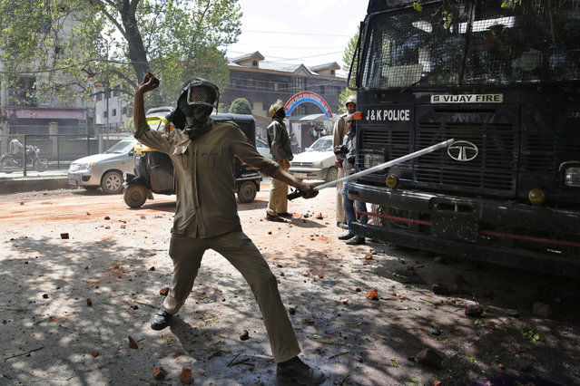 An Indian police man throws stones at protesters supporting students as they clash in Srinagar, Indian controlled Kashmir, Monday, April 24, 2017. (Photo by Mukhtar Khan/AP Photo)