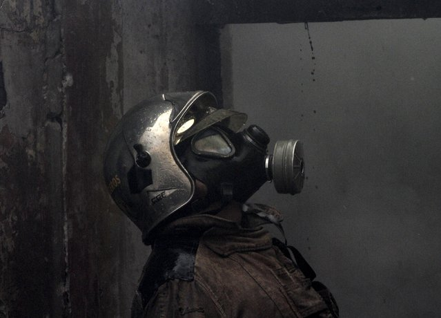 A fire fighter looks at the fire in a popular district of La Paz, July 17, 2015. (Photo by David Mercado/Reuters)
