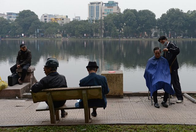 This picture taken on January 18, 2016 shows a street barber (R) serving a customer at a public park in downtown Hanoi. From Soviet-style letters of denunciation to outlandish rumours of a coup, Hanoi is abuzz with political gossip ahead of a key leadership change this week that has plunged the ruling communist elite into turmoil. (Photo by Hoang Dinh Nam/AFP Photo)