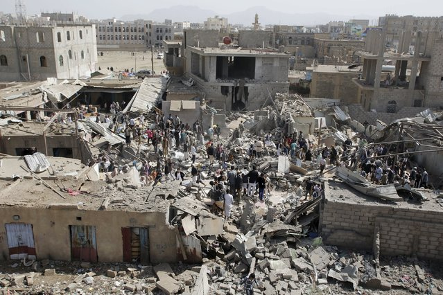 People and vendors gather upon the rubble of shops destroyed by a Saudi-led air strike that hit a marketplace in Yemen's capital Sanaa July 20, 2015. (Photo by Khaled Abdullah/Reuters)