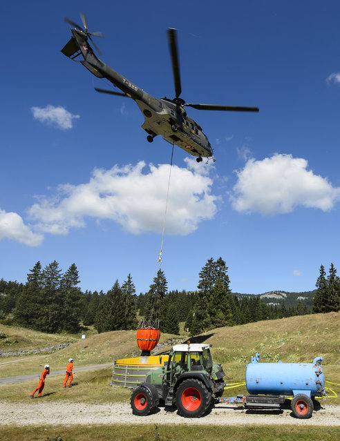 A helicopter of the Swiss Army delivers water from a reservoir in the region of Marchairuz, Switzerland, Tuesday, July 21 2015. Soldiers have been ordered to help keep cows in the far west of the country cool amid a weeklong heat wave. (Photo by Jean-Christophe Bott/Keystone via AP Photo)