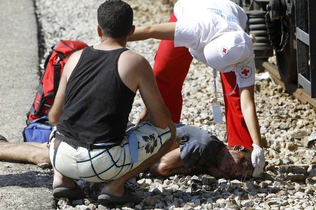 In this photo taken on Thursday, July 23, 2015 Red Cross workers gives the first aid to a migrant who has been seriously injured after he climbed atop of a tank wagon where he suffered an electric shock, in the southern Macedonian town of Gevgelija. (Photo by Boris Grdanoski/AP Photo)