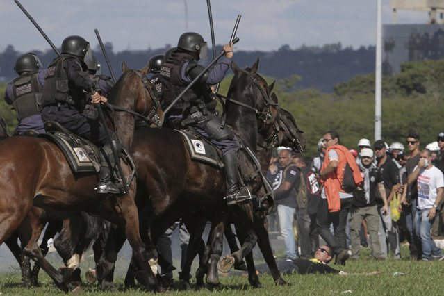 Mounted police charge demonstrators during an anti-government protest in Brasilia, Brazil, Wednesday, May 24, 2017. (Photo by Eraldo Peres/AP Photo)