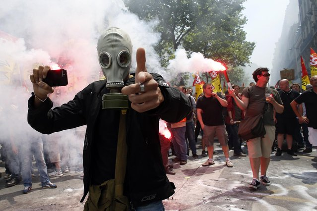 A protester wearing a gas mask holds a smartphone and gestures during a demonstration by striking employees of the French state rail company SNCF near the Transport Ministry in Paris on June 12, 2014, on the second day of a nation-wide strike to protest a government railway reform project. (Photo by Thomas Samson/AFP Photo)