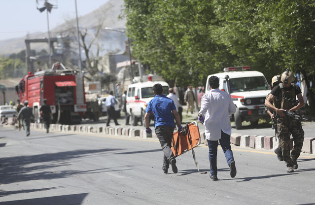 Medic personnel run to the site of an explosion in Kabul, Afghanistan, Wednesday, May 31, 2017. A massive explosion rocked a highly secure diplomatic area of Kabul on Wednesday morning, causing casualties and sending a huge plume of smoke over the Afghan capital. (Photo by Massoud Hossaini/AP Photo)