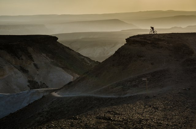"""""""Adventure awaits"""". It was the end of a long, epic mountain bike ride through the Negev desert in Israel when we arrived at the Tzaror mountain lookout. Our guide continued to the """"official"""" lookout on the next hill, while all of us just stopped at the first moment we saw the fantastic view. The setting sun lighting up the bit of haze between the hills on the horizon gave the perfect backdrop for our guide on the hill. Photo location: Tzaror mountain lookout, Negev desert, Israel. (Photo and caption by Ilan Shacham/National Geographic Photo Contest)"""