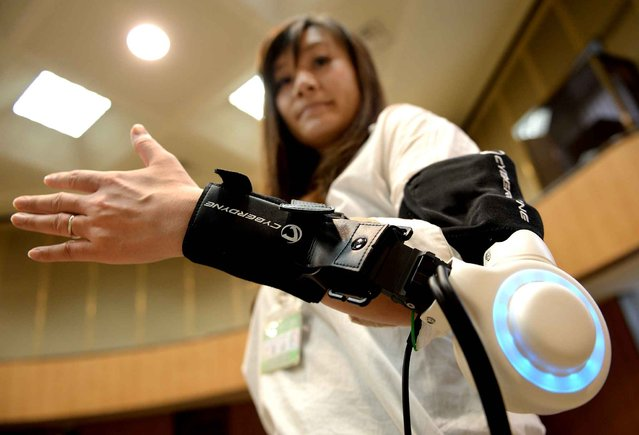 An official of Kawasaki City demonstrates a new powered exoskeleton to assist movement of an arm developed by Japan's robot suit venture Cyberdyne during a press conference in Kawasaki, suburb of Tokyo, on June 18, 2014. Cyberdyne on June 18 teamed up with the major industrial city of Kawasaki in a drive to speed up integration of robotic technology in real society. (Photo by Toru Yamanaka/AFP Photo)