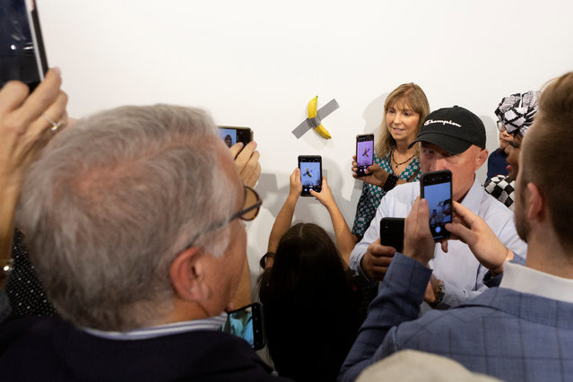 """A woman poses for a photo next to a banana attached with duct-tape that replaces the artwork """"Comedian"""" by the artist Maurizio Cattelan, which was eaten by David Datuna, in Miami Beach, Florida, December 7, 2019. (Photo by Eva Marie Uzcategui/Reuters)"""