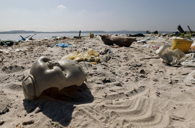 A piece of a toy doll is seen on Fundao beach in the Guanabara Bay in Rio de Janeiro, Brazil, July 30, 2015. Rio de Janeiro continues to face criticism locally and abroad that the bodies of water it plans to use for competition in the 2016 Olympic Games are too polluted to host events. Untreated sewage and trash frequently find their way into the Atlantic waters of Copacabana Beach and Guanabara Bay – both future sites to events such as marathon swimming, sailing and triathlon events. (Photo by Sergio Moraes/Reuters)