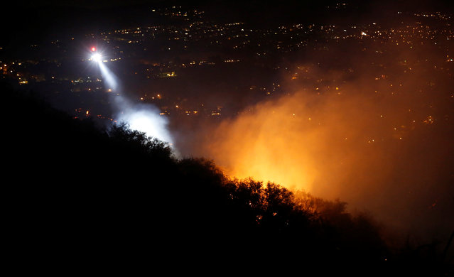"""A helicopter flies over a hotspot while battling the """"Old Fire"""" burning in Calabasas, California, U.S., June 4, 2016. (Photo by Mario Anzuoni/Reuters)"""