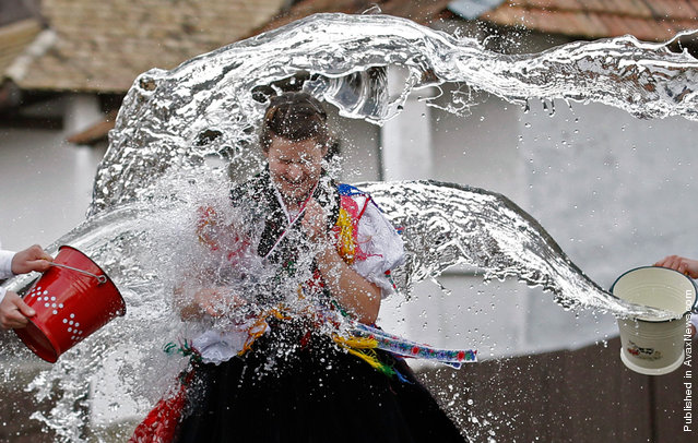 """A woman runs as men throw water at her as part of traditional Easter celebrations in Holloko, Hungary, 100 km (62 miles) east of Budapest, on April 14, 2011. Locals from the World Heritage village of Holloko celebrate Easter with this traditional """"watering of the girls"""", a tribal fertility ritual rooted in the area's pre-Christian past"""